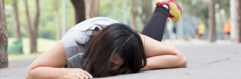 A woman lies facedown after a slip and fall accident on a paved walkway