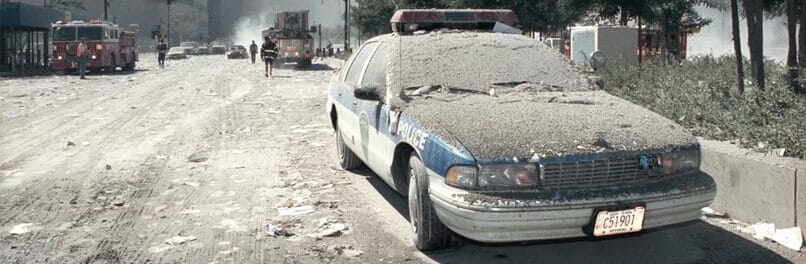 Toxic dust coats the landscape around ground zero, including a police car and the street