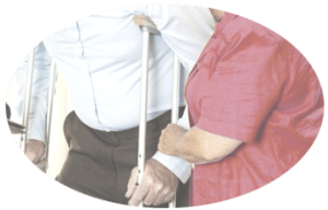 An elderly man on crutches is assisted by a health aide