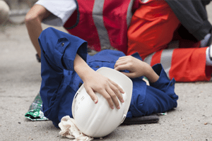 A victim of a labor law and construction accident lies on the ground after being injured