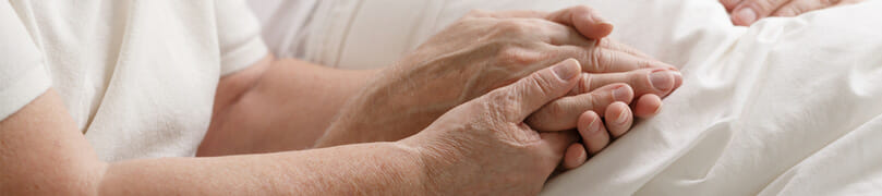 An elderly couple holds hands as they cope with Uloric side effects