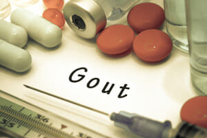 "Pills and vials of medications surround the word ""gout"""