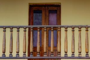 A wooden balcony railing, which is at least 36 inches high to meet building code
